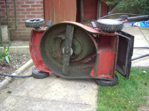 A typical rotary lawnmower on its side showing the blade.